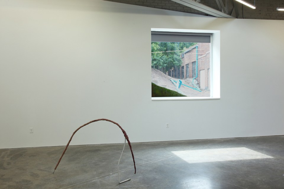 Left: Andrew Boatright, Tilte d'Arc, 2014, Old metal pipe, aluminum foil, polyurethane adhesive, wood stain. Right: Mike Black, Disregard Series #13, 2014, Rain gutter, spray paint