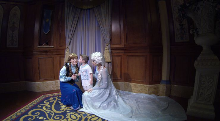 Carson gives a kiss to Anna and Elsa at Magic Kingdom