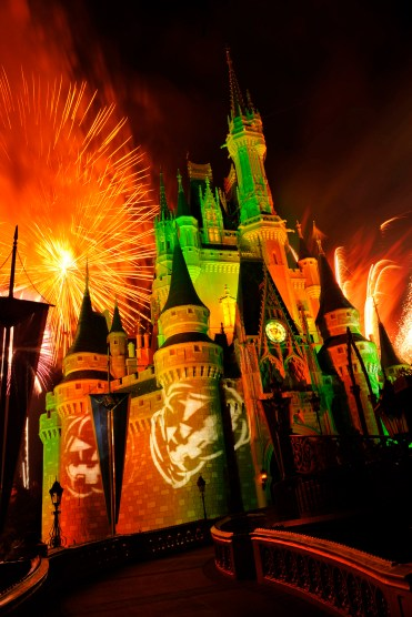 "Orange fireworks explode over Cinderella Castle while illuminated pumpkins are projected with light during the ""Happy HalloWishes"" fireworks show. The show is part of ""Mickey's Not-So-Scary Halloween Party,"" an after-hours Halloween celebration at the theme park. A separate ticket is required to attend. (Gene Duncan, photographer)"