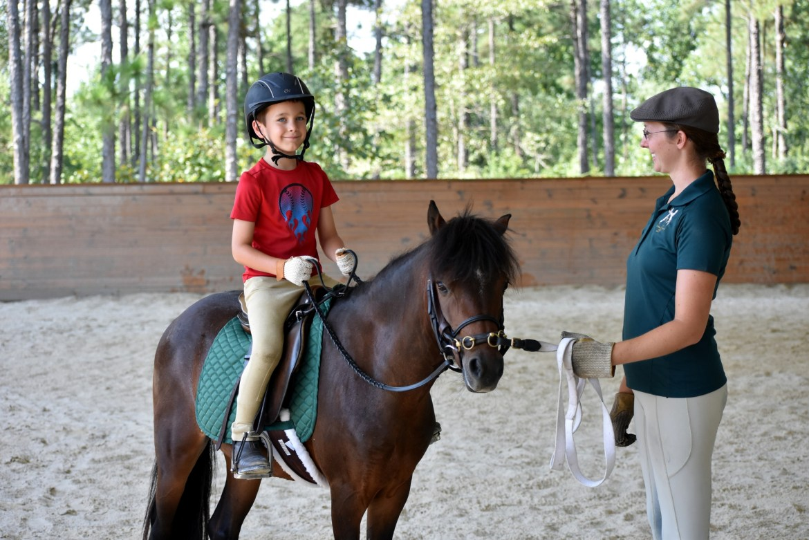 Young boy sits on pony taking part in riding lesson on lounge line