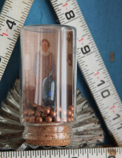 Detail of flash bulb, copper BBs, photo in corked bottle, ruler, and tart tin.