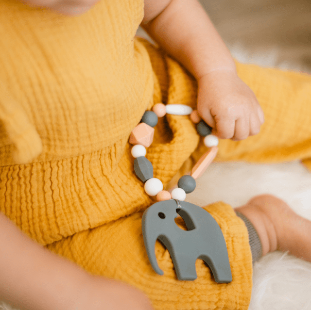 Baby holding a teething toy elephant
