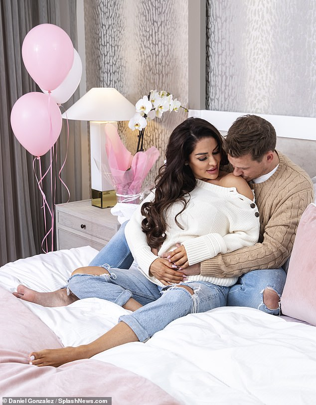 Doting: Posing on their bed, the couple switched outfits once again, donning matching light-wash jeans with distressed knees