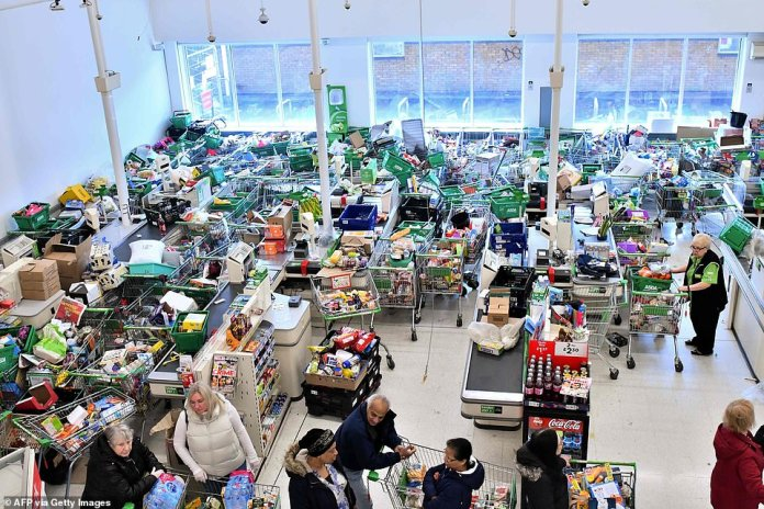 Trolleys piled high for deliveries are seen as shoppers queue at the checkout of Asda in London amid coronavirus hysteria in March last year
