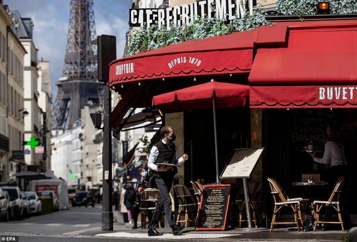A waiter serves guests outside a cafe near the Eiffel Tower in Paris last week after restaurants reopened in the French capital