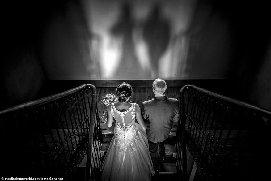 Coming together: Isma Sanchez, also from Spain, documented the final few moments before a father gave away his beloved daughter at her wedding, with the pair seen ascending some steps at the venue