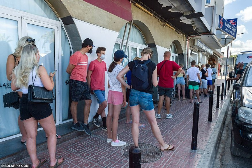 Holidaymakers can be seen queueing outside a clinic inSan Antonio to get PCR tests ahead of their flights back to the UK