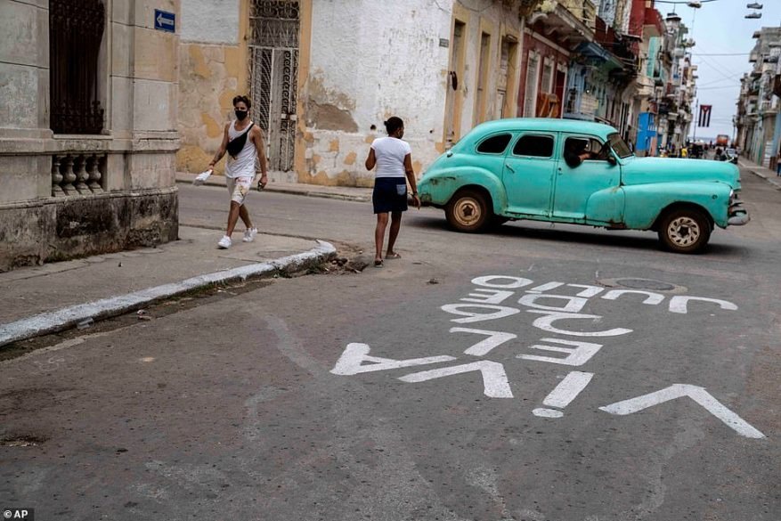 A vintage car inHavana, Cuba, which has strict entry requirements for foreign visitors. The graffiti on the road is a slogan commemorating leader Fidel Castro