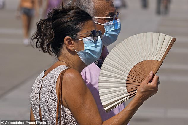 A woman fans herself in Madrid, Spain, Tuesday, as temperatures begin to rise at the start of an oncoming heatwave