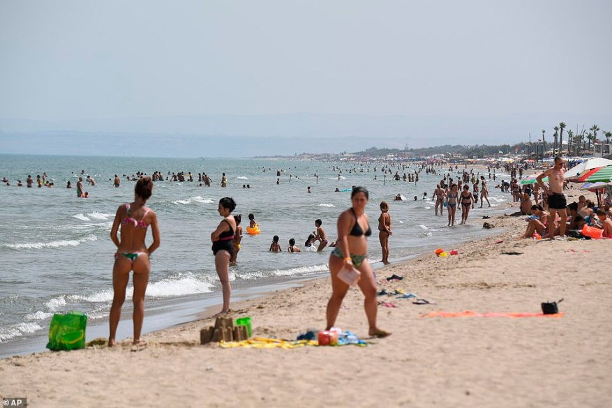 People enjoy a cool dip in the sea as anticyclone Lucifer swept through Italy on Thursday, bringing blistering heats of over 119F