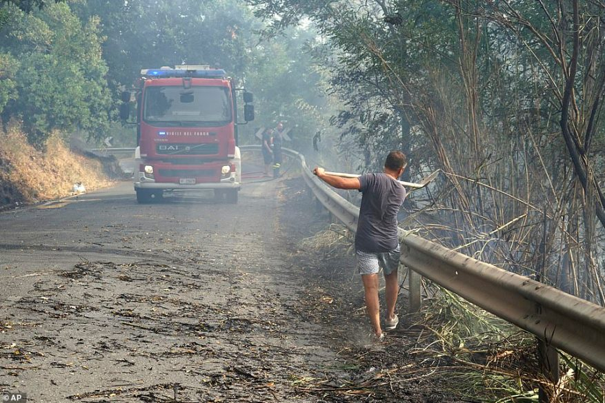 A volunteer helps firefighters control wild blazes in Fuscaldo, in Calabria, Italy, on Wednesday after flames were ignited by hot weather