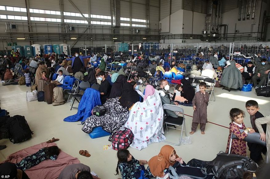 Women and children are seen sitting inside a hangar at Ramstein. The men sleep in tents, while the women are housed indoors