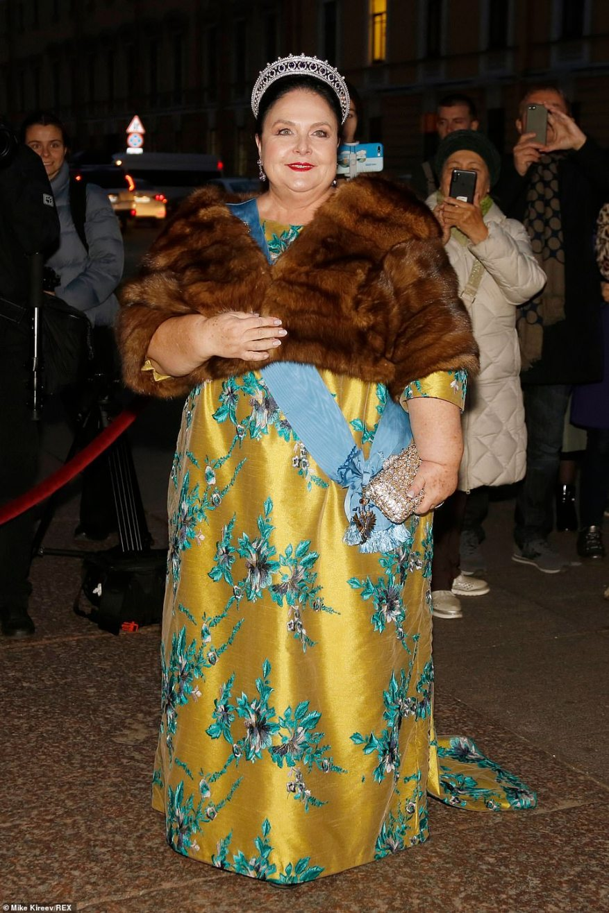 Quick change! After wearing a blue skirt and coat to the religious ceremony, the mother of the groom Duchess MariaVladimirovna changed into a golden gown with rich floral embroidery and wrapped up in a fur stole for the evening festivities.