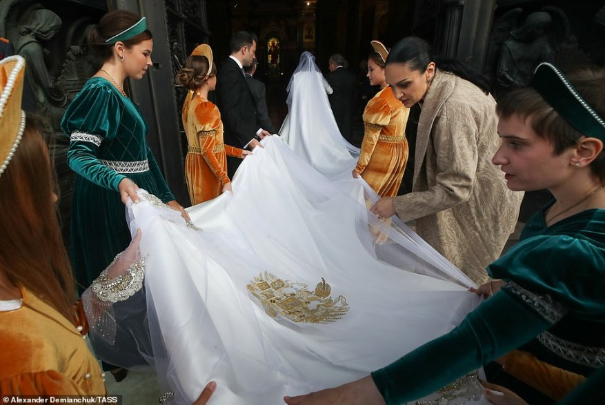 The bridal party, dressed in velvet green and orange gowns, could be seen carrying the lengthy train and veil of the gown (pictured).