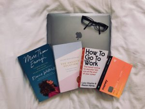 Self-help books next to glasses on top of laptop