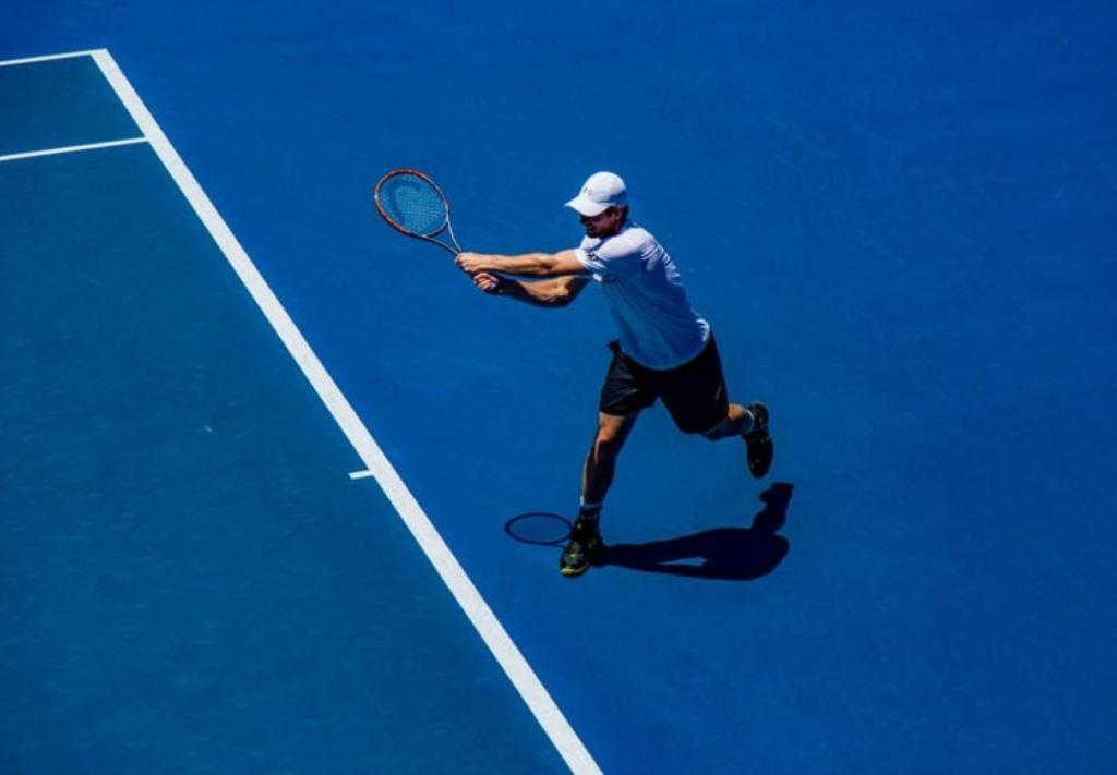 Mężczyzna grający w tenisa na niebieskiej nawierzchni typu hard court