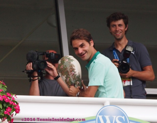 Roger Federer balcony joking around miming tossing trophy listening to crowd roar photos pictures