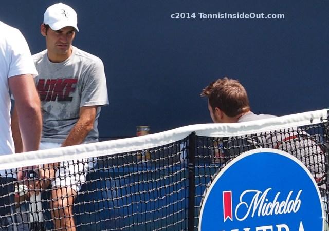 Federer stare Wawrinka crouched down kneeling behind net practice