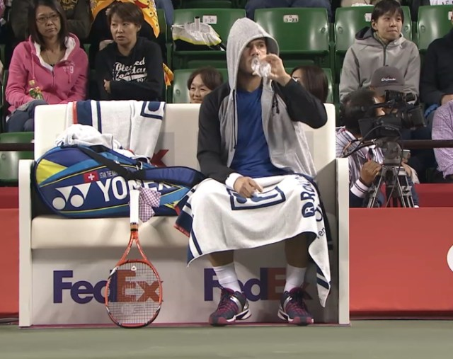 Stan Wawrinka in hoodie drinking water bottle towel draped across legs Yonex racquet bag