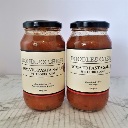 Two full jars of tomato pasta sauce on white background
