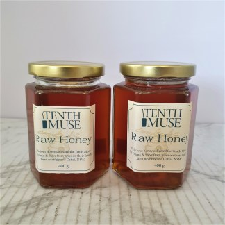 Two full jars of honey on a white background
