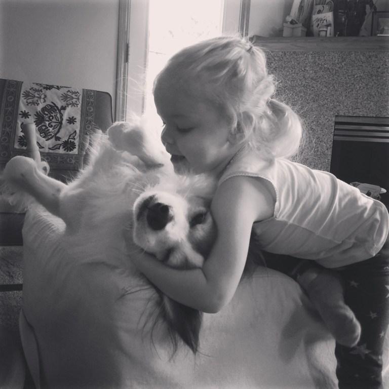 preschooler and dog hug