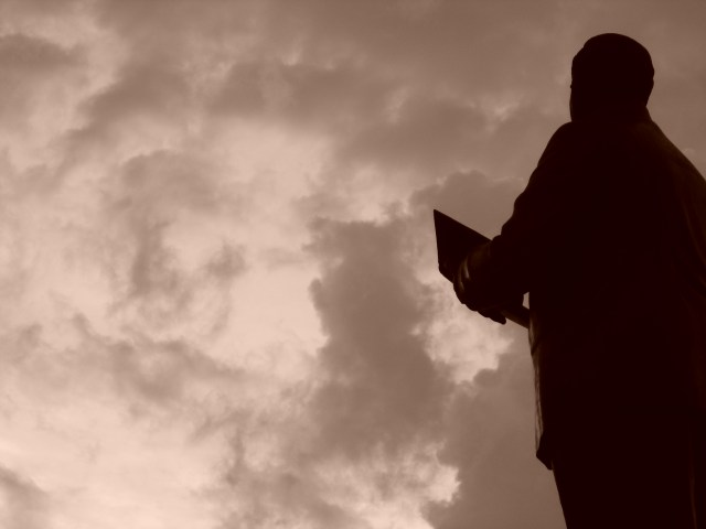Man holding Bible and looking skyward.