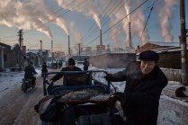 Chinese men pull a tricycle in a neighborhood next to a coal-fired power plant in Shanxi, China. Photo: Kevin Frayer