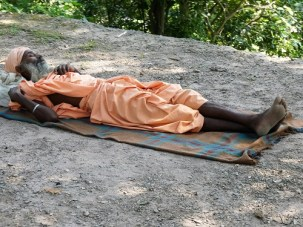 A wandering yogi sleeps by the roadside near Vashistha Gufa Cave, North of Rishikesh