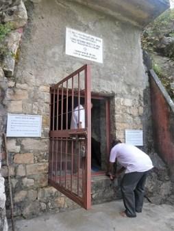 Two men pilgrims enter Babaji's cave to meditate.