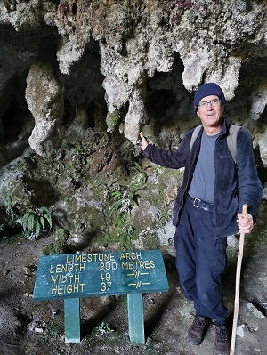 Manfred beside the stalactites in the Oparara arch cavern and the arch sign