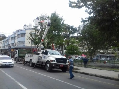 Utilizando caminhão com cesto aéreo, funcionários retiram ervas de passarinho das árvores que embelezam a Praça Olímpica