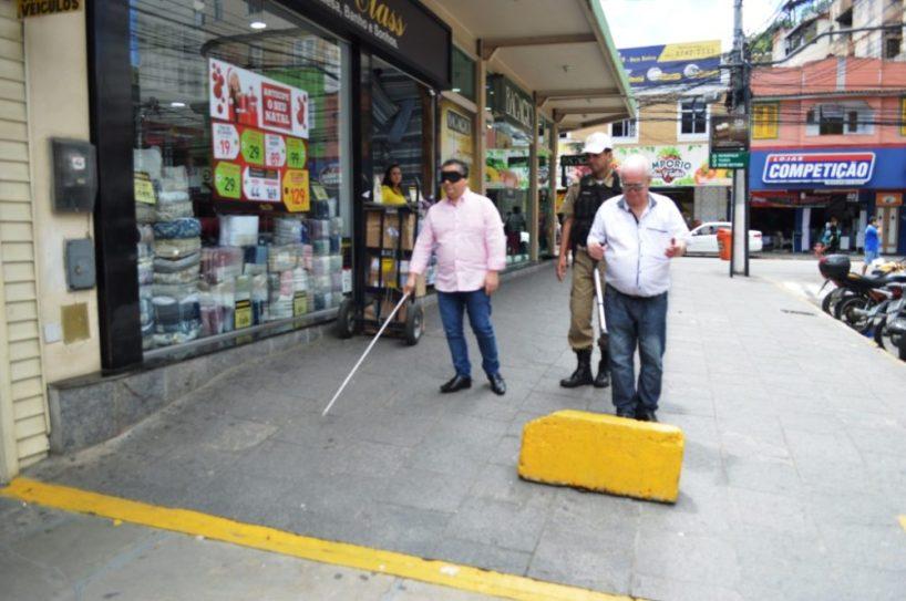 Com venda nos olhos, prefeito em exercício Sandro Dias segue por trecho de calçada na Rua Duque de Caxias