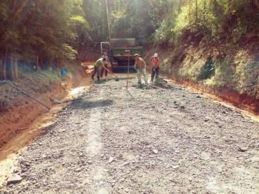 Trabalhadores da Agricultura espalham fresa de asfalto em trecho de estrada na zona rural