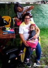 A cabeleireira voluntária Tatiane Lopes prepara Adriana Abreu para o atendimento gratuito