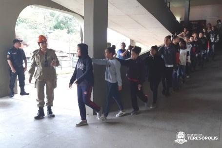 Alunos saem do prédio escolar em fila, seguindo a orientação repassada