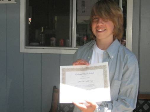the author's son, smiling and holding a diploma