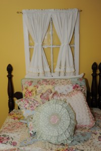 photo of a bed with fancy pillows and curtains over the headboard
