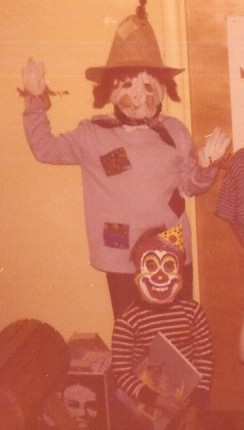the author, at age 10, wearing a homemade scarecrow costume, with her brother, wearing a clown mask
