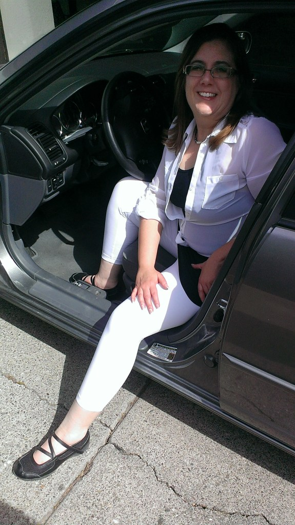 photo of the author sitting half inside a car, wearing white Lysse capri leggings with a black dress and white tie over shirt