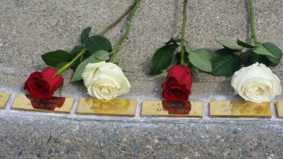 photo of four plaques for the four slain officers with roses over each plaque