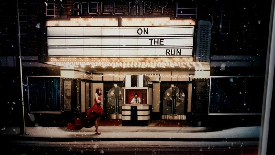 """photo of a woman wearing a Lego dress, waiting in the snow outside a movie theater with the marquee """"On the Run"""""""