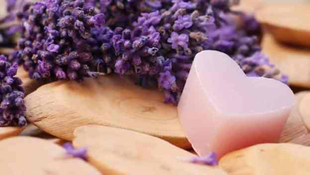 lavender and a soap in the shape of heart on the wood