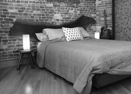Bedroom set at side angle with two lights in loft setting with hardwood floor brick background and birch leaf inlayed resin panel