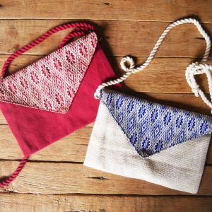 Sur la photo se trouvent deux sacs Nikemoui un de chaque couleur. Un rouge orné d'une frise rouge et blanche et un sac blanc et son rabat bleu et blanc.