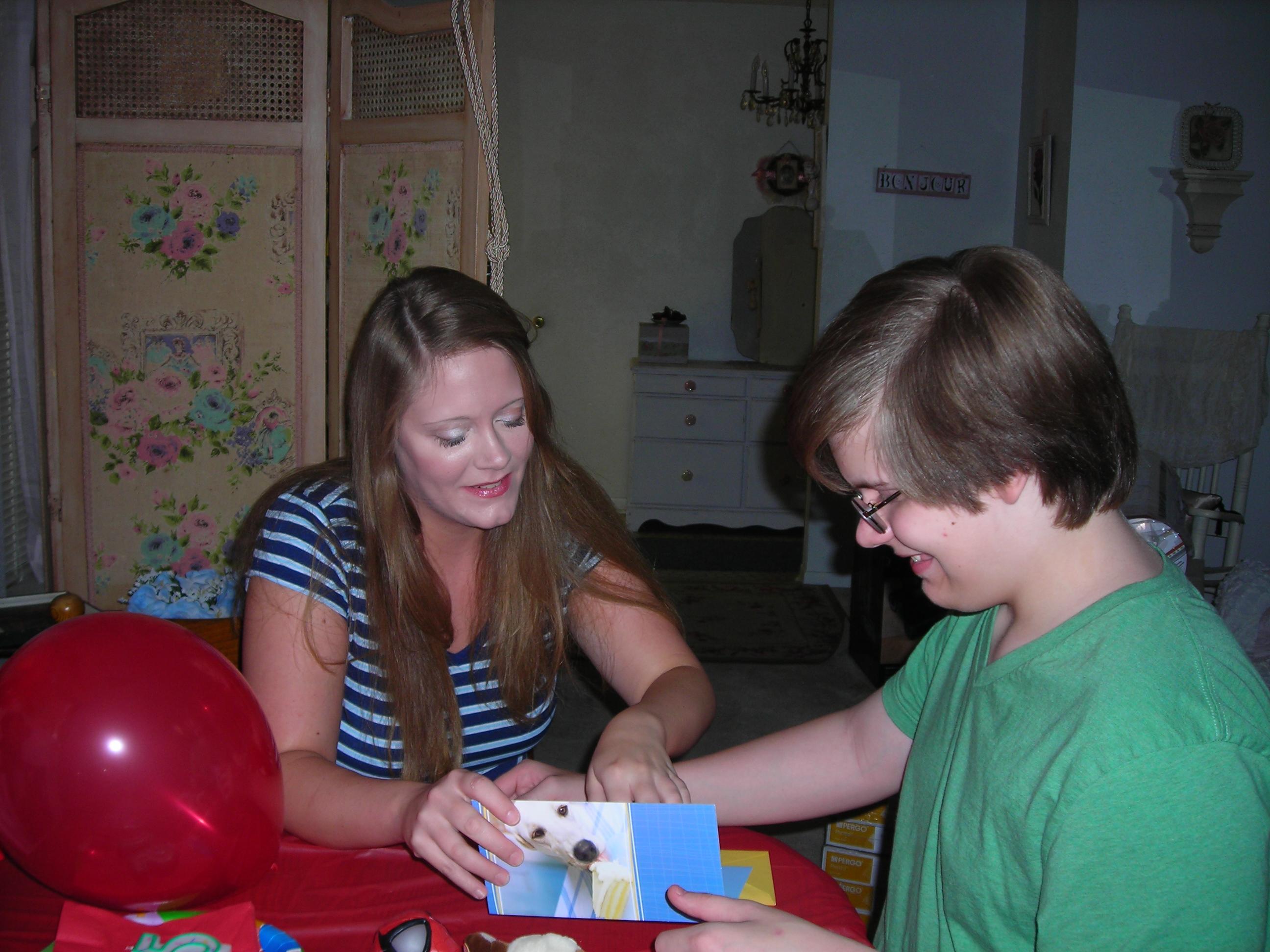 Big sister Tara shows Matt his birthday card