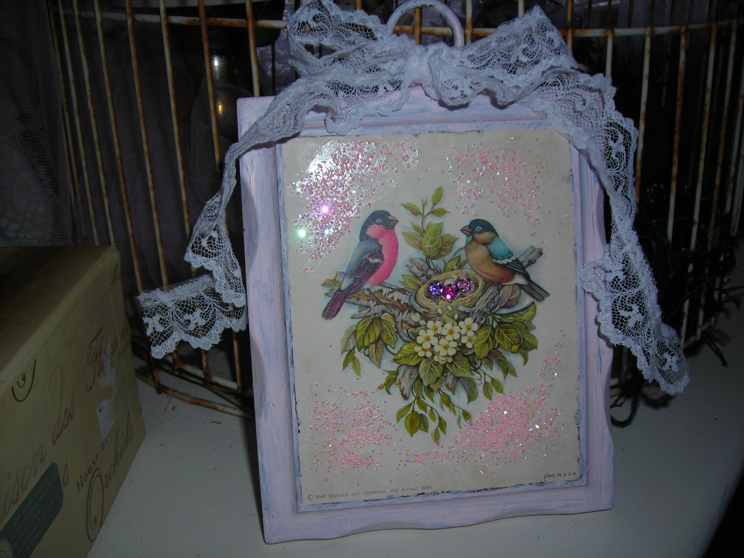 found this birdie picture at the GW barn. painted the dark wood, added pink glitter, bling in the nest and some lace. now she looks great in my bird collection