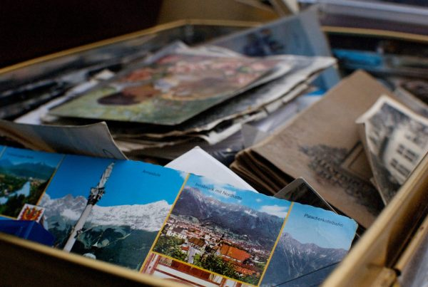pile of old pictures and postcards in a brown box