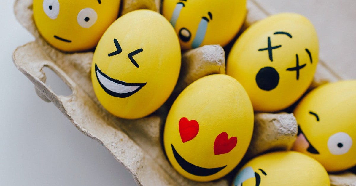 eggs in a carton that are painted like emojis