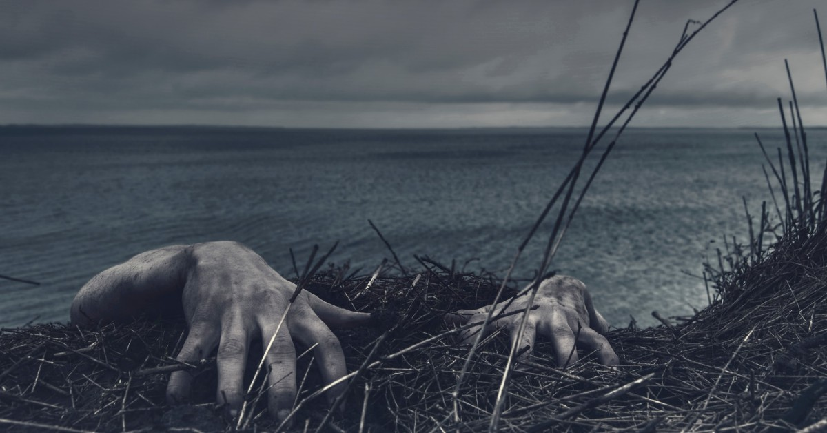 Eerie hands clinging to dry grass